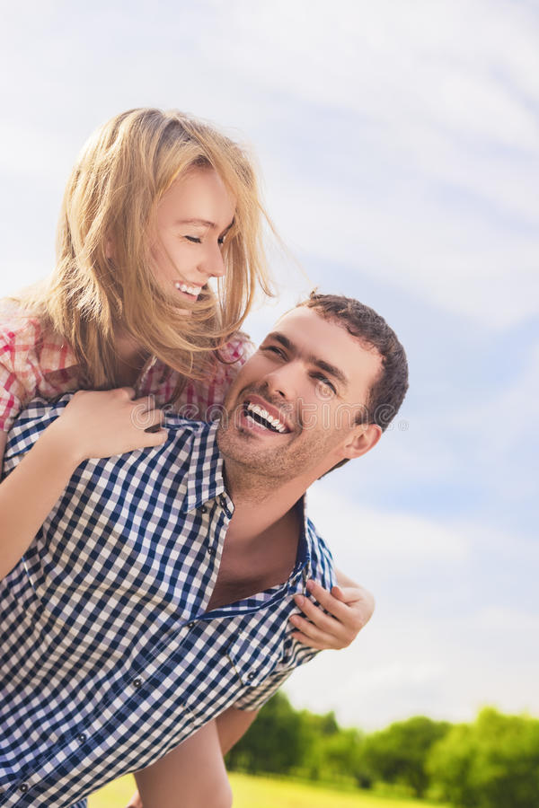 Πορτρέτο του ευτυχούς και εύθυμου νέου καυκάσιου ζεύγους Piggybacki στοκ εικόνα με δικαίωμα ελεύθερης χρήσης