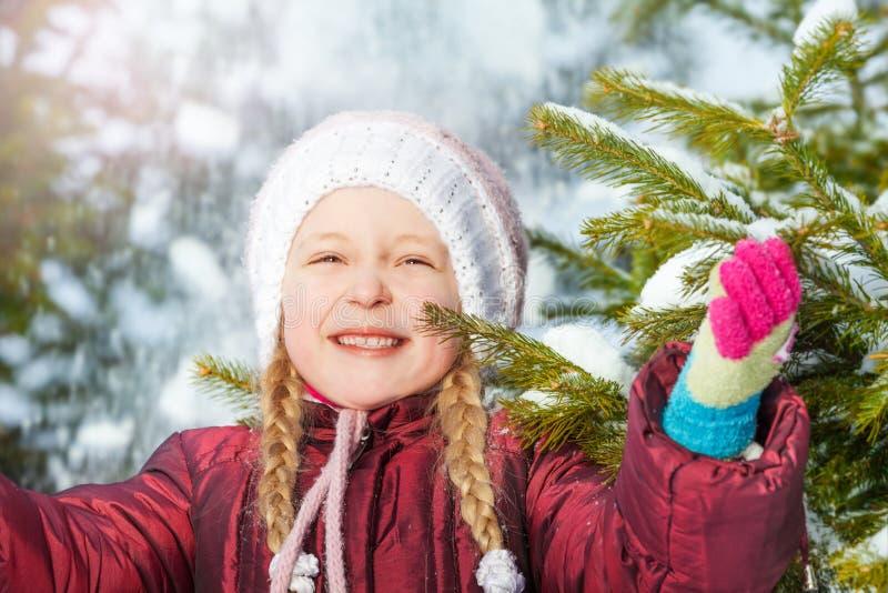 Πορτρέτο του ευτυχούς κοριτσιού με το δέντρο και το χιόνι έλατου στοκ φωτογραφία