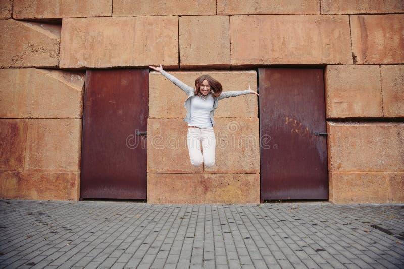 Πορτρέτο του ευτυχούς νέου άλματος γυναικών υπαίθρια στοκ φωτογραφία