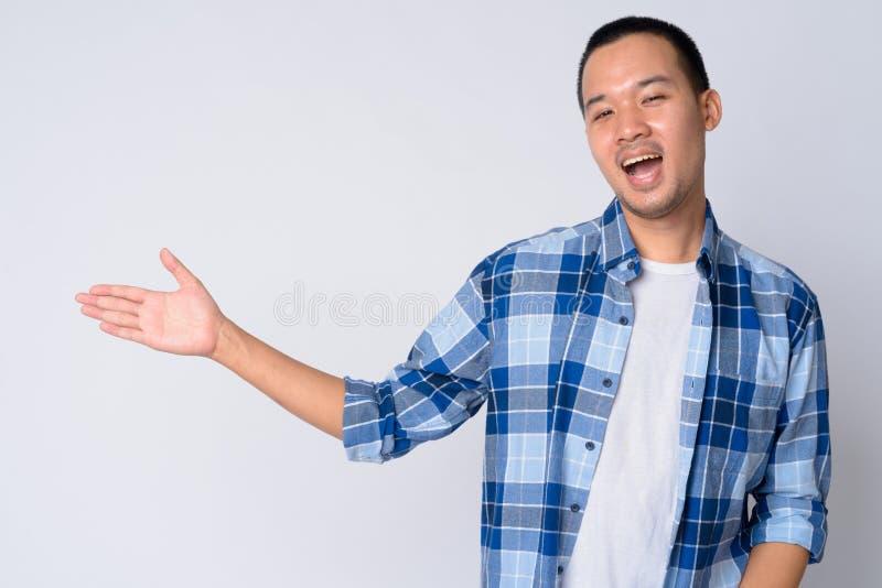 Πορτρέτο του ευτυχούς νέου ασιατικού ατόμου hipster που παρουσιάζει κάτι στοκ φωτογραφία με δικαίωμα ελεύθερης χρήσης