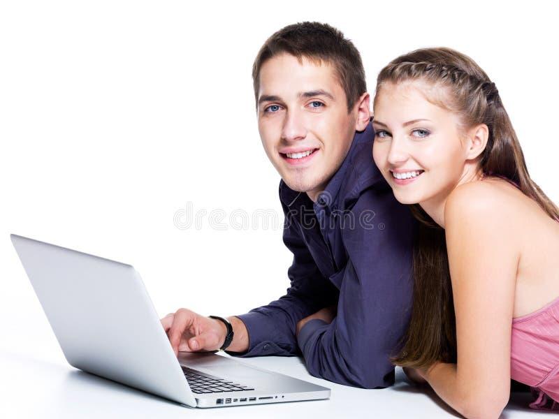 Πορτρέτο του ευτυχούς νέου ζεύγους με το lap-top στοκ εικόνες