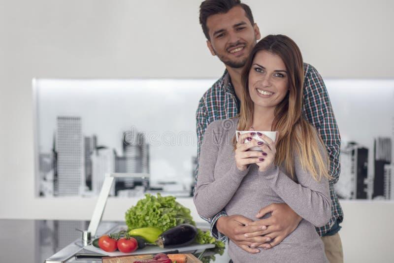 Πορτρέτο του ευτυχούς νέου μαγειρέματος ζευγών μαζί στην κουζίνα στο σπίτι στοκ φωτογραφίες με δικαίωμα ελεύθερης χρήσης