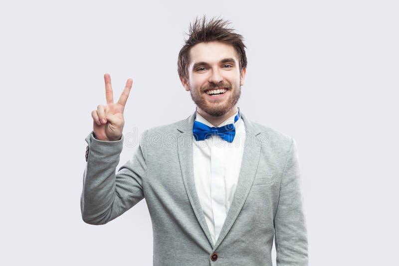 Πορτρέτο του ευτυχούς οδοντωτού όμορφου γενειοφόρου ατόμου smiley στο περιστασιακό γκρίζο κοστούμι, μπλε δεσμός τόξων που στέκετα στοκ εικόνες με δικαίωμα ελεύθερης χρήσης