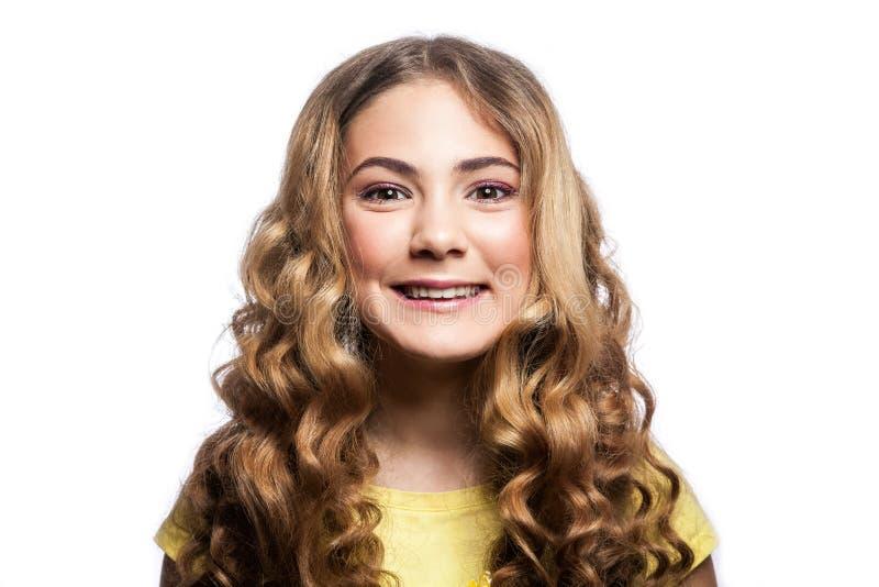 Πορτρέτο του ευτυχούς οδοντωτού κοριτσιού smiley με το κυματιστό hairstyle και την κίτρινη μπλούζα στοκ φωτογραφία με δικαίωμα ελεύθερης χρήσης