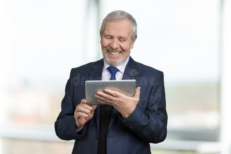 Πορτρέτο του ευτυχούς παλαιού επιχειρηματία που χρησιμοποιεί την ταμπλέτα στοκ εικόνα με δικαίωμα ελεύθερης χρήσης
