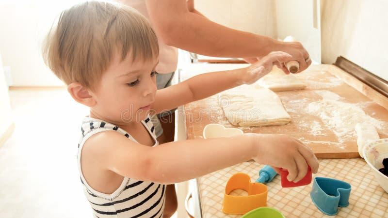 Πορτρέτο του ευτυχούς χαμογελώντας αγοριού μικρών παιδιών με το νέο ψήσιμο και το μαγείρεμα μητέρων στην κουζίνα Διδασκαλία και ε στοκ εικόνες με δικαίωμα ελεύθερης χρήσης