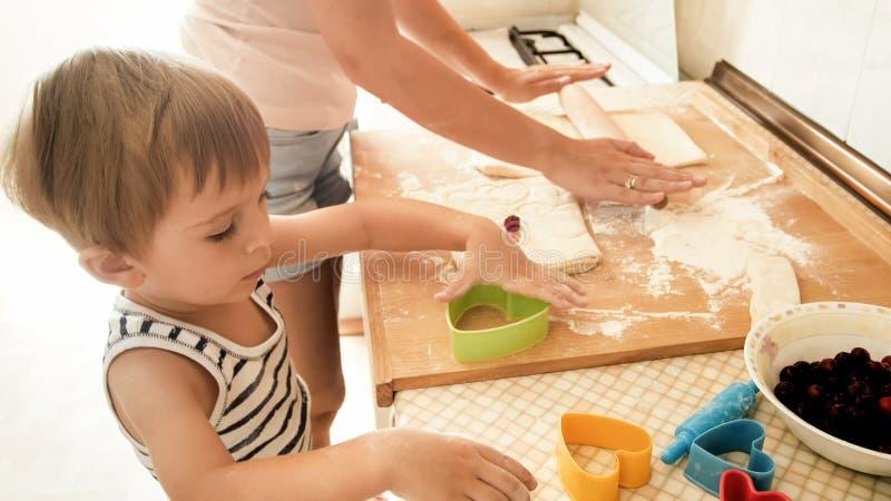 Πορτρέτο του ευτυχούς χαμογελώντας αγοριού μικρών παιδιών με το νέο ψήσιμο και το μαγείρεμα μητέρων στην κουζίνα Διδασκαλία και ε στοκ εικόνες
