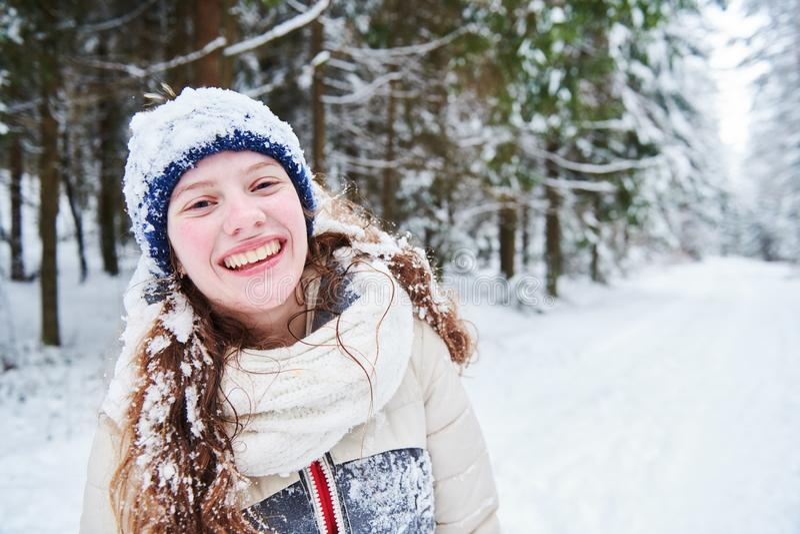 Πορτρέτο του ευτυχούς χαμογελώντας κοριτσιού στο χειμερινό χιονώδες δάσος στοκ φωτογραφία