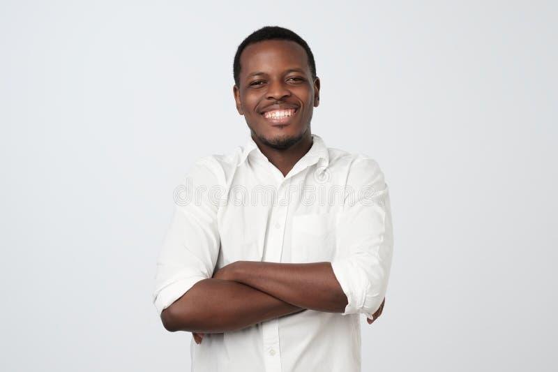 Πορτρέτο του ευτυχούς όμορφου αφρικανικού ατόμου στο άσπρο πουκάμισο που διασχίζει τα χέρια στοκ εικόνες με δικαίωμα ελεύθερης χρήσης