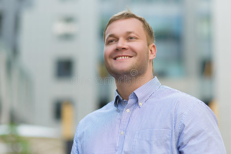 Πορτρέτο του ευτυχούς όμορφου επιχειρηματία στο μπλε πουκάμισο υπαίθριο στοκ φωτογραφία με δικαίωμα ελεύθερης χρήσης