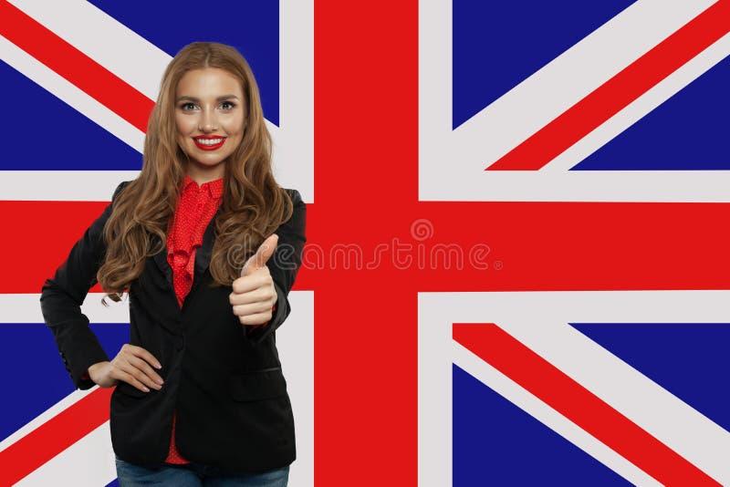 Πορτρέτο του ευτυχούς όμορφου κοριτσιού με τον αντίχειρα επάνω στο υπόβαθρο βρετανικών σημαιών Νέα αγγλική γλώσσα εκμάθησης γυναι στοκ εικόνα