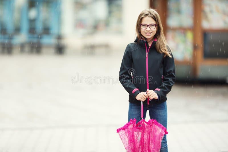 Πορτρέτο του ευτυχούς όμορφου νέου κοριτσιού προ-εφήβων με τη ρόδινη ομπρέλα κάτω από τη βροχή στοκ εικόνα