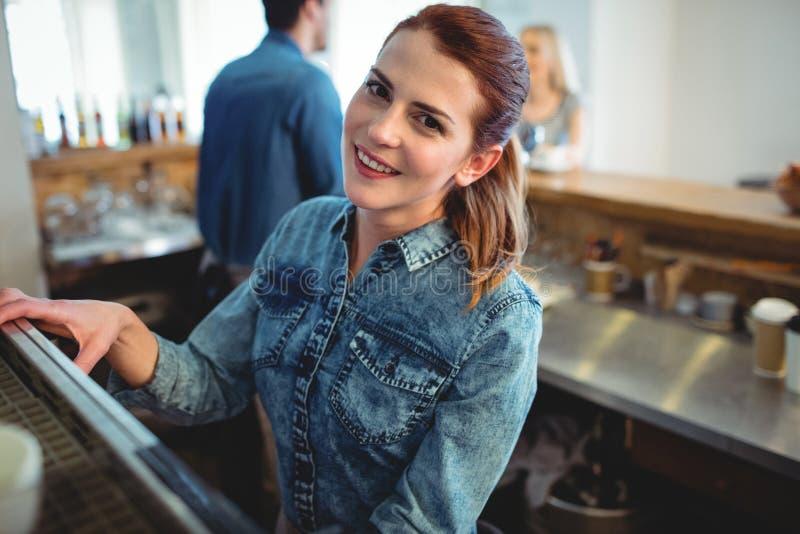 Πορτρέτο του ευτυχούς barista με το συνάδελφο και τον πελάτη στον καφέ στοκ φωτογραφίες
