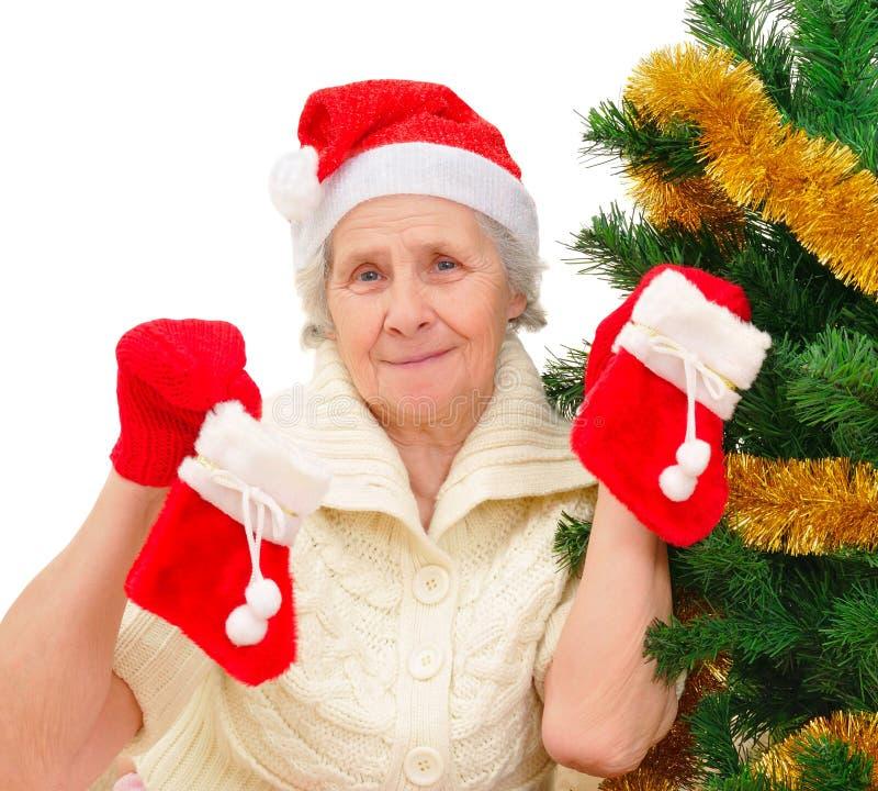 Πορτρέτο του ευτυχούς grandma σε Santa ΚΑΠ που διακοσμεί το χριστουγεννιάτικο δέντρο στοκ εικόνες με δικαίωμα ελεύθερης χρήσης