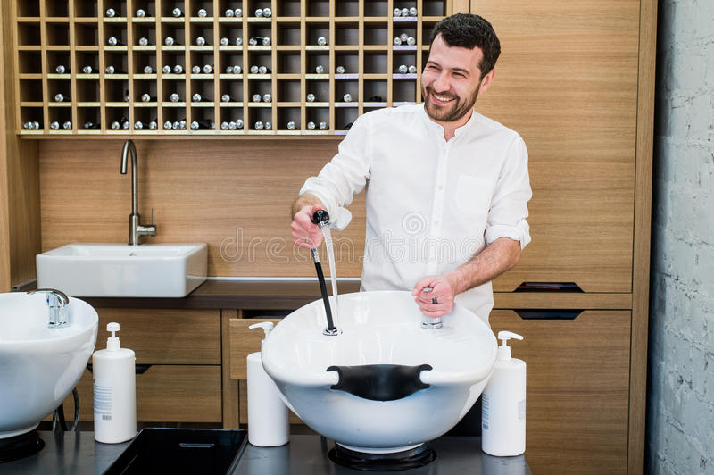 Πορτρέτο του ευτυχούς hairstylist με τον κοντινό νεροχύτη κρουνών στο σαλόνι barbershop στοκ φωτογραφία