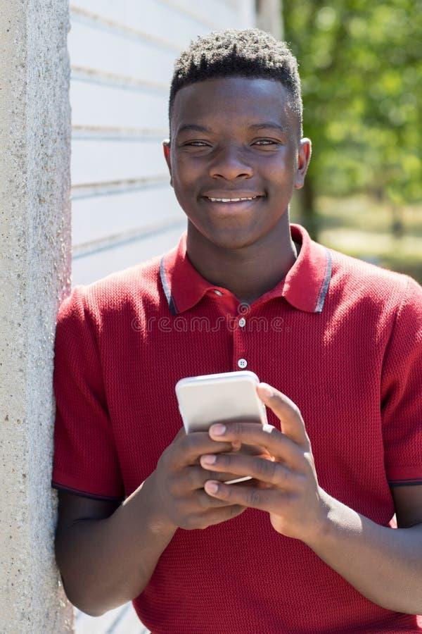 Πορτρέτο του εφήβου που στέλνει υπαίθρια το μήνυμα κειμένου από τη Mobil στοκ φωτογραφίες με δικαίωμα ελεύθερης χρήσης