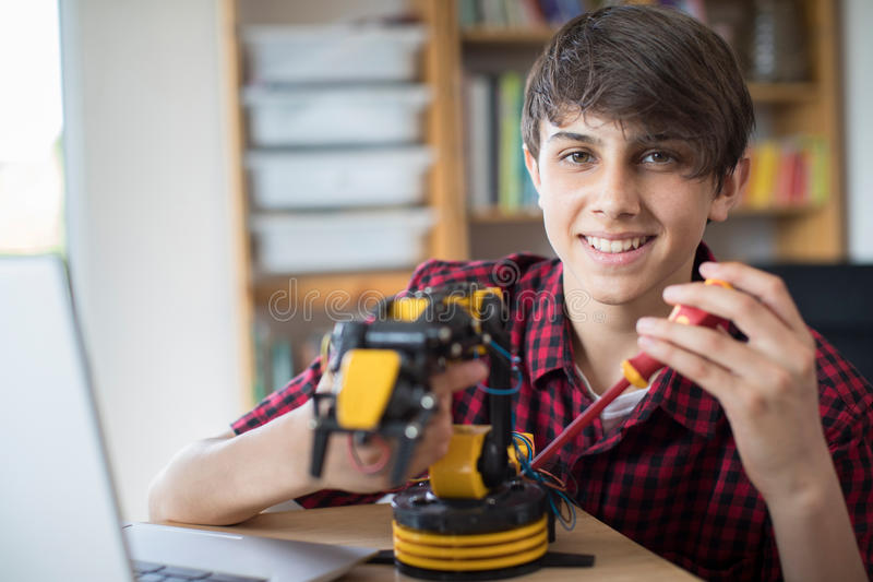 Πορτρέτο του εφήβου που χτίζει το ρομποτικό βραχίονα στο σχολείο στοκ εικόνα με δικαίωμα ελεύθερης χρήσης