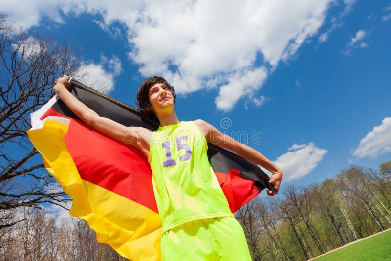 Πορτρέτο του εφηβικού αθλητικού τύπου που κυματίζει τη γερμανική σημαία στοκ φωτογραφία με δικαίωμα ελεύθερης χρήσης