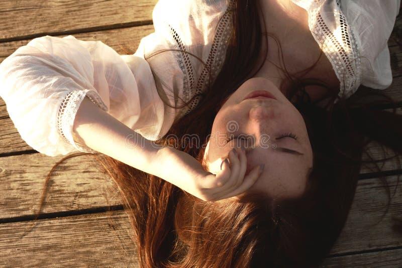 Πορτρέτο του εφηβικού πρότυπου κοριτσιού ομορφιάς με την κόκκινη τρίχα στο φως ήλιων με τις φακίδες Ηλιοφάνεια Αναδρομικά φωτισμέ στοκ εικόνες με δικαίωμα ελεύθερης χρήσης