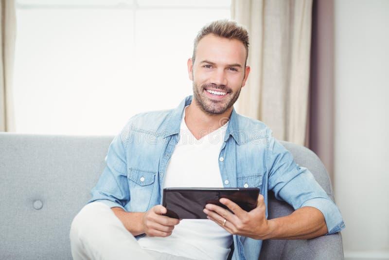 Πορτρέτο του εύθυμου ατόμου που κρατά την ψηφιακή ταμπλέτα στοκ εικόνα