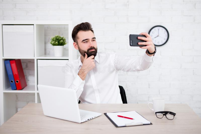 Πορτρέτο του εύθυμου γενειοφόρου επιχειρηματία ή του σπουδαστή χρησιμοποιώντας το lap-top και παίρνοντας selfie τη φωτογραφία στοκ εικόνες