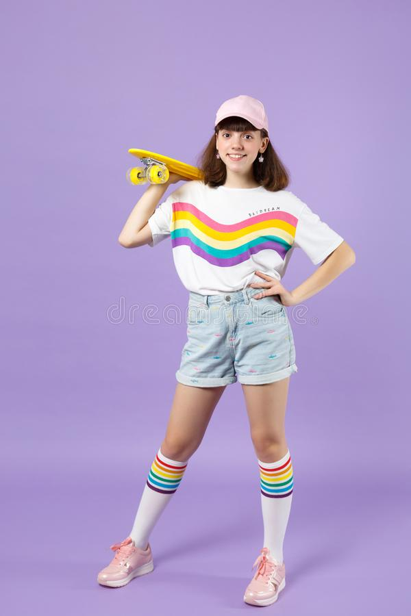 Πορτρέτο του εύθυμου κοριτσιού εφήβων στα ζωηρά ενδύματα που στέκονται, που κρατά κίτρινο skateboard απομονωμένο στον ιώδη τοίχο  στοκ φωτογραφία με δικαίωμα ελεύθερης χρήσης