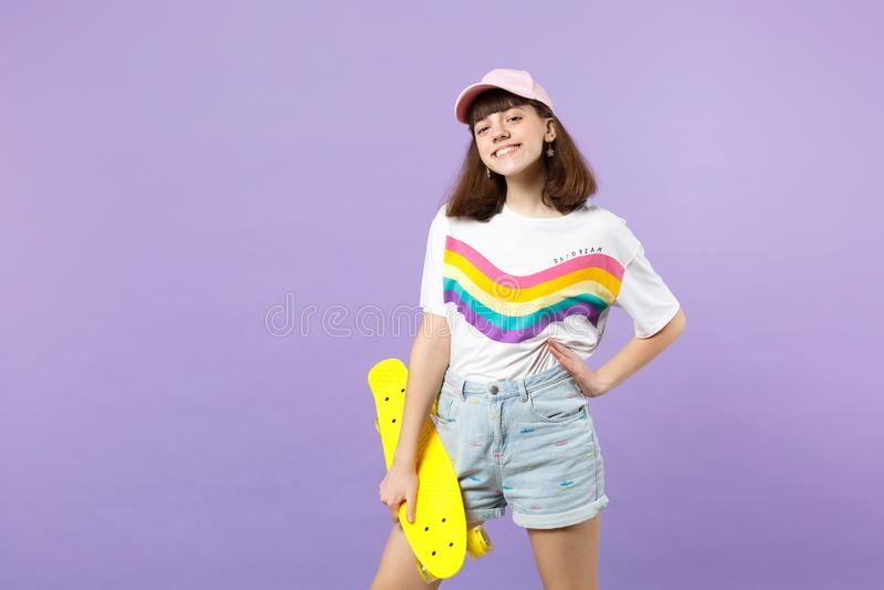 Πορτρέτο του εύθυμου χαμογελώντας κοριτσιού εφήβων στα ζωηρά ενδύματα που κρατά κίτρινο skateboard απομονωμένο στον ιώδη τοίχο κρ στοκ εικόνα
