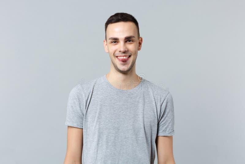 Πορτρέτο του εύθυμου χαμογελώντας νεαρού άνδρα στα περιστασιακά ενδύματα που παρουσιάζουν γλώσσα, που φαίνεται κάμερα που απομονώ στοκ εικόνα με δικαίωμα ελεύθερης χρήσης