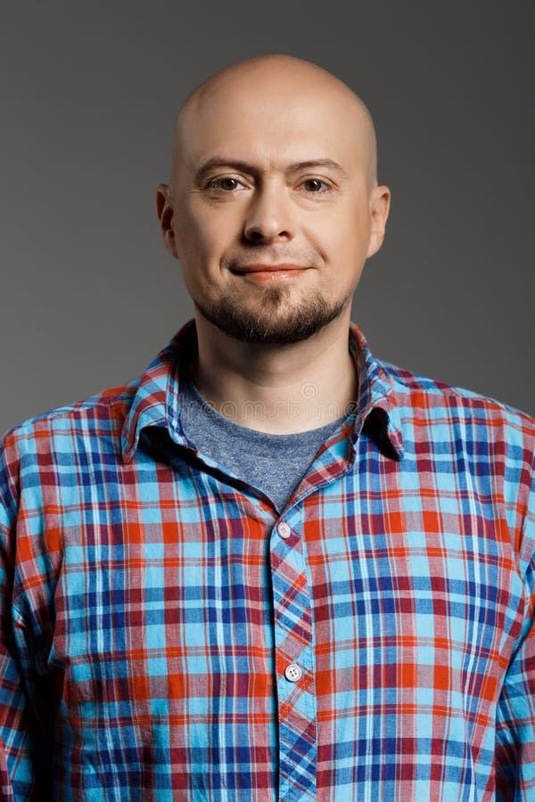 Πορτρέτο του εύθυμου όμορφου μέσης ηλικίας ατόμου στο πουκάμισο καρό που εξετάζει τη κάμερα που χαμογελά πέρα από το γκρίζο υπόβα στοκ εικόνες
