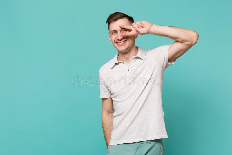 Πορτρέτο του εύθυμου όμορφου νεαρού άνδρα στα περιστασιακά ενδύματα που παρουσιάζουν σημάδι νίκης που απομονώνεται στον μπλε τυρκ στοκ εικόνες