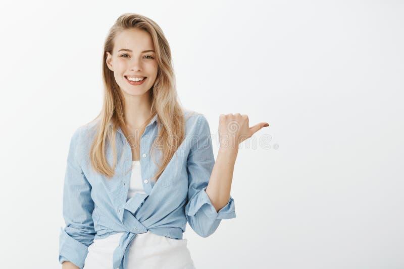 Πορτρέτο του θετικού όμορφου ευρωπαϊκού κοριτσιού με τα ξανθά μαλλιά στο μοντέρνο πουκάμισο, που αυξάνει το χέρι και που δείχνει  στοκ φωτογραφία