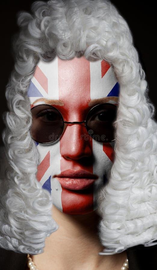 Πορτρέτο του θηλυκού αγγλικού δικηγόρου με τη χρωματισμένα βρετανικά σημαία και τα γυαλιά ηλίου του Union Jack στοκ εικόνες