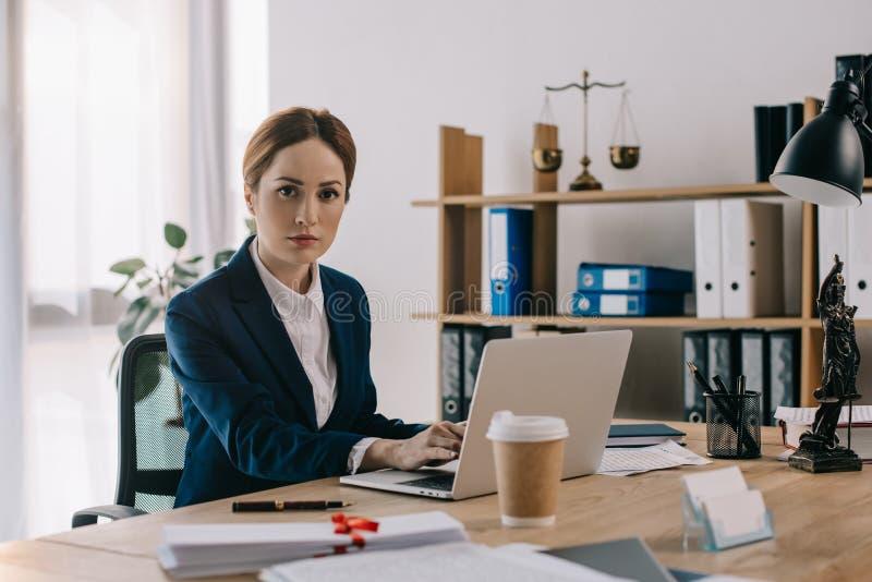 πορτρέτο του θηλυκού δικηγόρου στο κοστούμι που εξετάζει τη κάμερα στον εργασιακό χώρο στοκ φωτογραφίες