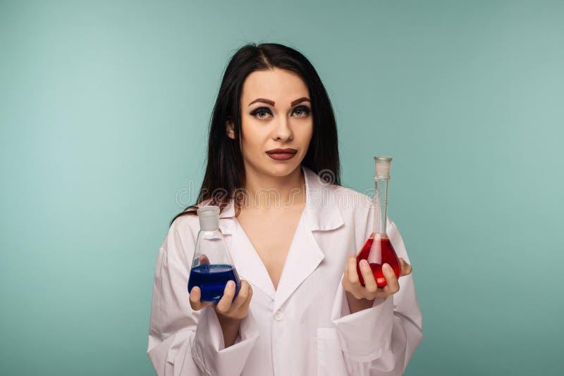Πορτρέτο του θηλυκού επιστήμονα που εξετάζει τις φιάλες με τις διαφορετικές χημικές ουσίες στο ιατρικό εργαστήριο στοκ εικόνα με δικαίωμα ελεύθερης χρήσης