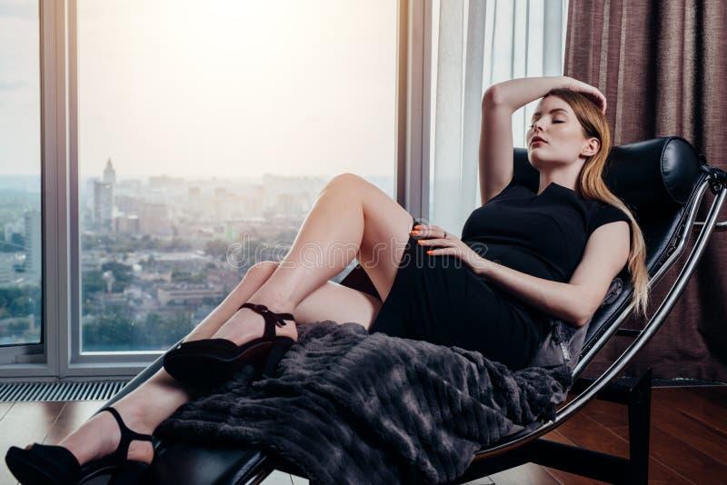 Πορτρέτο του θηλυκού προτύπου που φορά το απότομα μαύρο φόρεμα και τα υψηλά τακούνια που χαλαρώνουν στην καρέκλα στοκ φωτογραφία