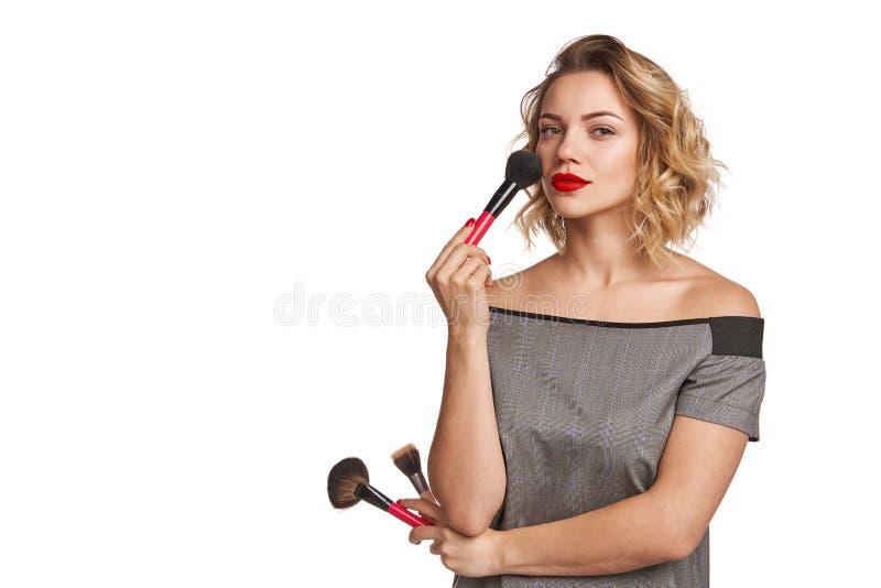 Πορτρέτο του θηλυκού στιλίστα που στέκεται με τις βούρτσες makeup στοκ φωτογραφία με δικαίωμα ελεύθερης χρήσης