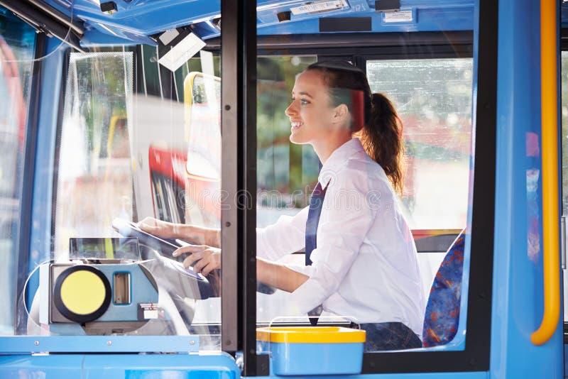 Πορτρέτο του θηλυκού οδηγού λεωφορείου πίσω από τη ρόδα στοκ εικόνες