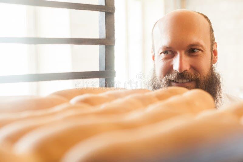 Πορτρέτο του ικανοποιημένου νέου ενήλικου αρτοποιού αρχιμαγείρων με τη μακριά γενειάδα στην άσπρη ομοιόμορφη στάση στο αρτοποιείο στοκ φωτογραφία με δικαίωμα ελεύθερης χρήσης