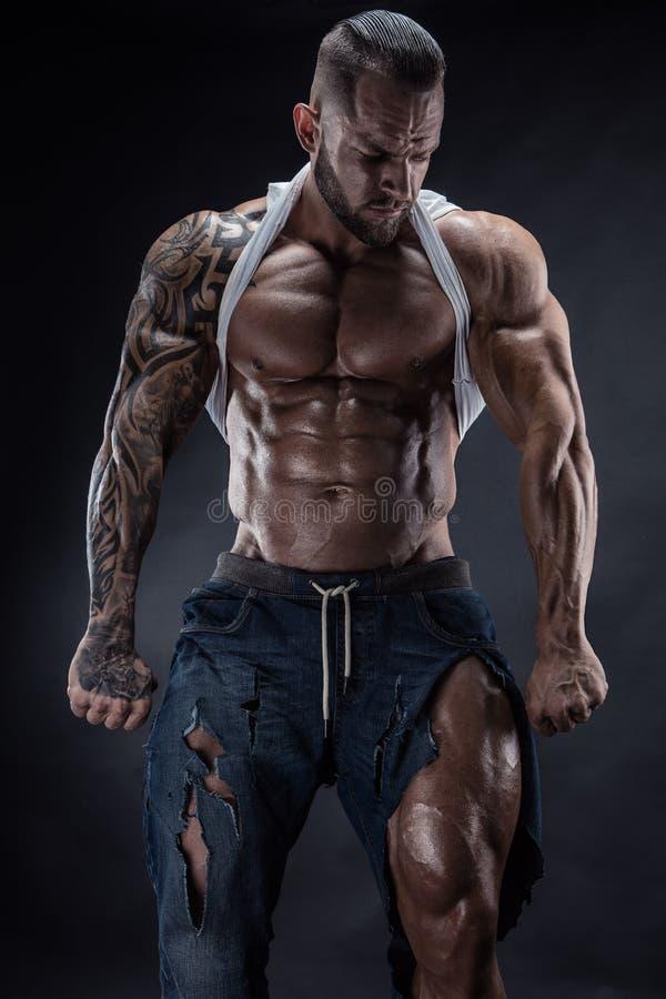 Πορτρέτο του ισχυρού αθλητικού ατόμου ικανότητας που παρουσιάζει μεγάλους μυς στοκ εικόνα