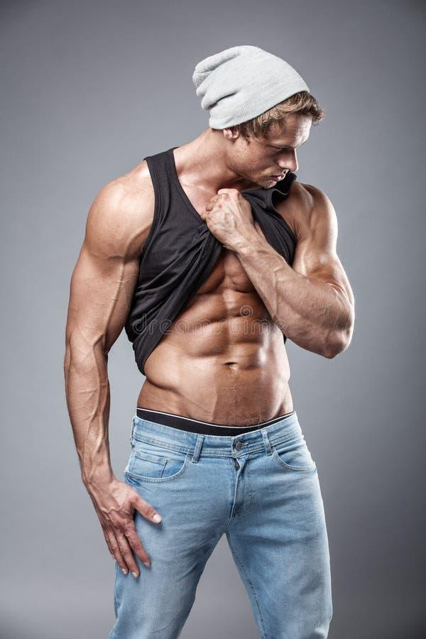 Πορτρέτο του ισχυρού αθλητικού ατόμου ικανότητας πέρα από το γκρίζο υπόβαθρο στοκ φωτογραφία