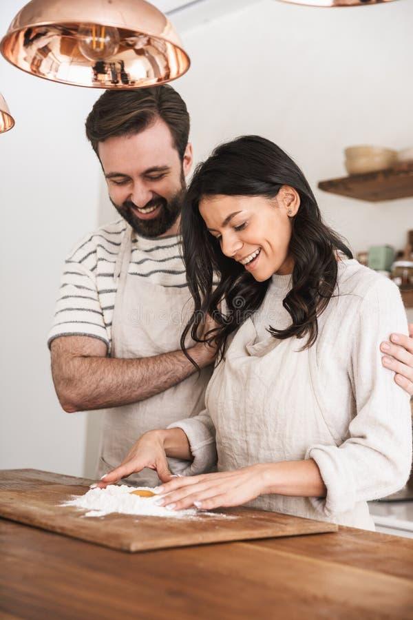 Πορτρέτο του καυκάσιου ζεύγους που φορά τις ποδιές που μαγειρεύουν τη ζύμη με το αλεύρι και τα αυγά στην κουζίνα στο σπίτι στοκ εικόνες