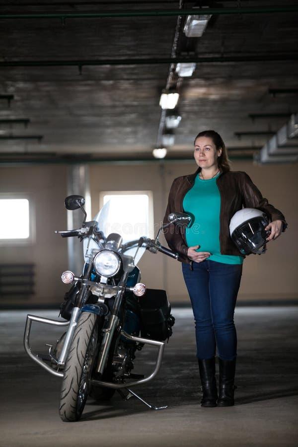 Πορτρέτο του καυκάσιου ποδηλάτη εγκύων γυναικών που στέκεται δίπλα στη μοτοσικλέτα με το άσπρο κράνος διαθέσιμο, τον υπόγειο χώρο στοκ φωτογραφίες με δικαίωμα ελεύθερης χρήσης