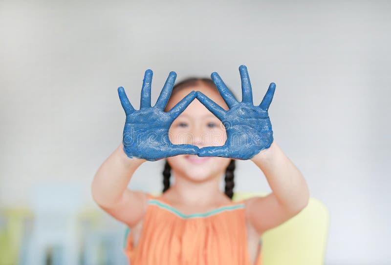 Πορτρέτο του κοιτάγματος μικρών κοριτσιών χαμόγελου των μπλε χεριών της που χρωματίζονται μέσω στο δωμάτιο παιδιών Εστίαση στα χέ στοκ φωτογραφία με δικαίωμα ελεύθερης χρήσης