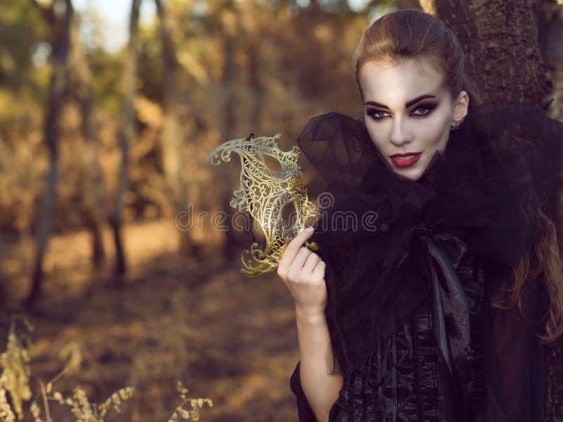 Πορτρέτο του κομψού επικίνδυνου γυναικείου βαμπίρ στα ξύλα που κρατούν τη λεπτή μάσκα και που φαίνονται ευθέα με το αρπακτικό βλέ στοκ φωτογραφία
