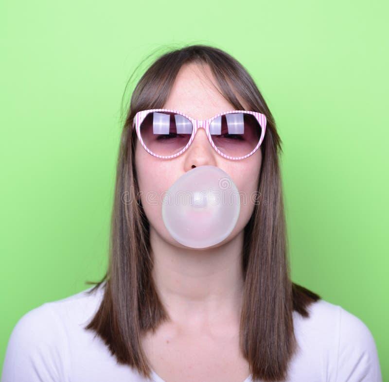 Πορτρέτο του κοριτσιού με τα γυαλιά που κάνουν το μπαλόνι με τη γόμμα φυσαλίδων στοκ εικόνα