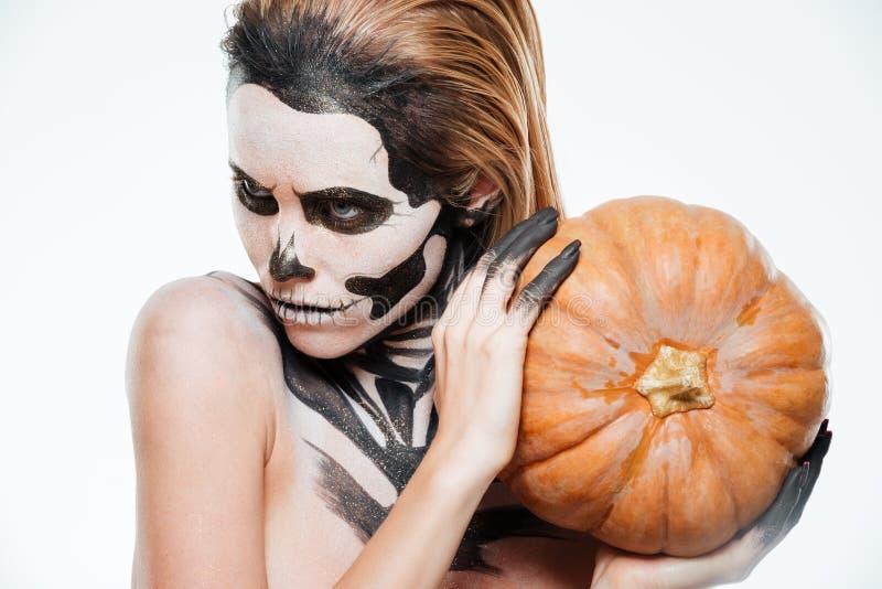 Πορτρέτο του κοριτσιού με την έντρομη κολοκύθα εκμετάλλευσης αποκριών makeup στοκ εικόνες