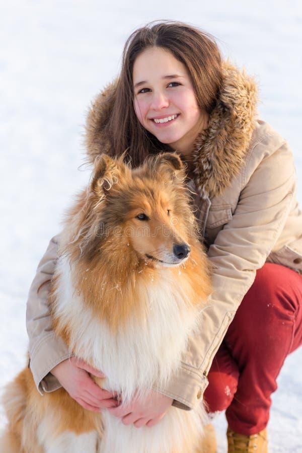 Πορτρέτο του κοριτσιού με το σκυλί κόλλεϊ στο τοπίο χιονιού στοκ εικόνα