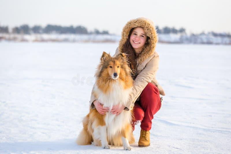 Πορτρέτο του κοριτσιού με το σκυλί κόλλεϊ στο χιονώδες τοπίο στοκ εικόνες