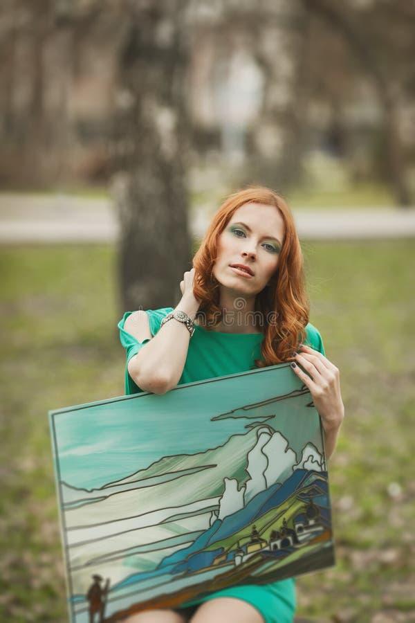 Πορτρέτο του κοριτσιού redhair στο πράσινο φόρεμα με τη νωπογραφία στα χέρια της στοκ φωτογραφίες