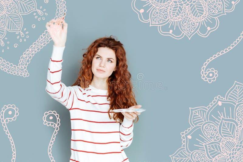 Πορτρέτο του λατρευτού κοριτσιού με τη σγουρή τρίχα που λειτουργεί στο σχέδιο τοίχων στοκ φωτογραφίες